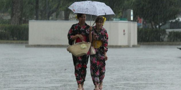 HIMEJI, JAPAN - JUNE 22: Japanese women dressed in 'Yukata' summer kimono's walk in a heavy rain during...