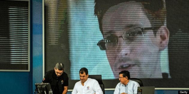 Rafael Correa, president of Ecuador, center, pauses during his weekly speech to the nation broadcast...