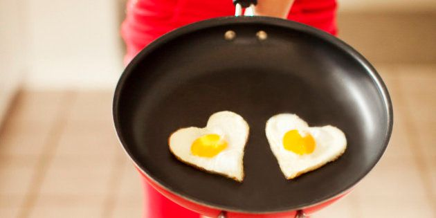 Woman dressed a red-patterend clothing holds a frying pan in front of her containing two heart-shaped