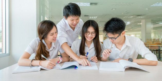 Group of Asian students in uniform studying together at