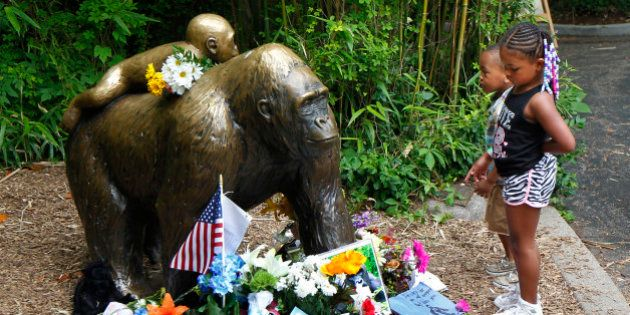 CINCINNATI, OH - JUNE 2: Visitors view a bronze statue of a gorilla and her baby surrounded by flowers...