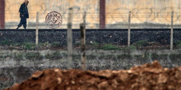 An armed man walks in IS-controlled Tal Abyad across the Turkish Akcakale border gate, Turkey, Saturday,...