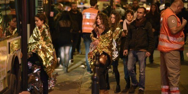 People are evacuated by bus, near the Bataclan concert hall in central Paris, on November 14, 2015. More...