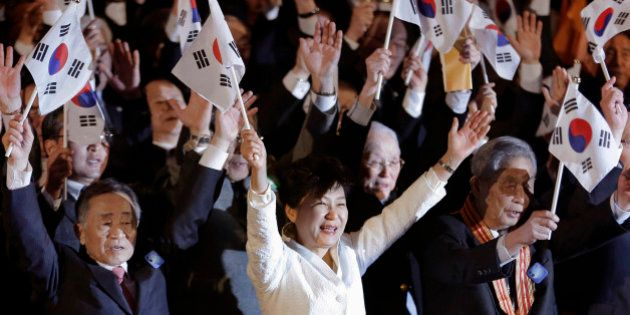 South Korean President Park Geun-hye, bottom center, gives three cheers with her national flag during...