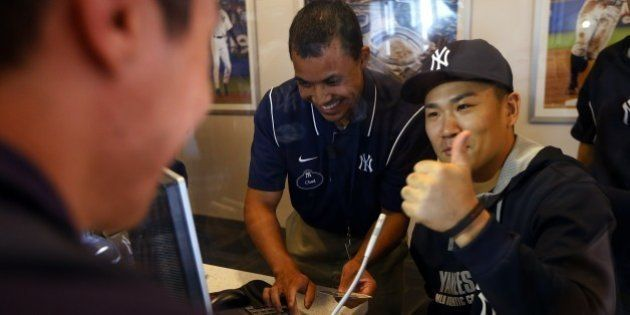 NEW YORK, NY - AUGUST 06: Pitcher Masahiro Tanaka #19 of the New York Yankees helps sell tickets in the...