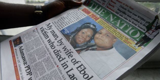 A man reads a newspaper featuring a front page story on the death of Liberian diplomat Patrick Sawyer...