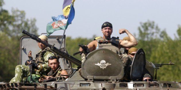 A serviceman postures on the APC located of the Ukrainian troops in Donetsk region on August 9, 2014....