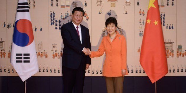 China's President Xi Jinping (L) shakes hands with his South Korean counterpart Park Geun-Hye (R) prior...