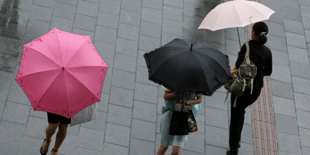 HIMEJI, JAPAN - AUGUST 10: Women walk through strong rain and wind delivered by Typhoon Halong on August...
