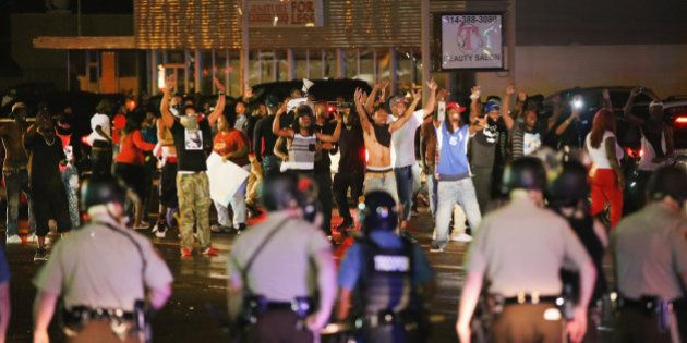 FERGUSON, MO - AUGUST 15: Demonstrators taunt police during a protest over the shooting death of Michael...