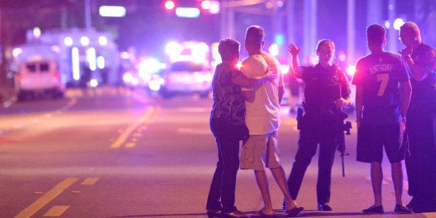 Orlando Police officers direct family members away from a multiple shooting at a nightclub in Orlando,...