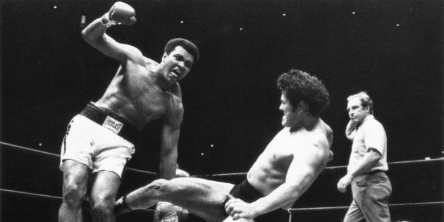 Japanese pro wrestler Antonio Inoki kicks the back of Muhammad Ali's leg in an attempt to trip him down...
