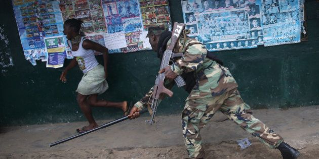 MONROVIA, LIBERIA - AUGUST 20: A Liberian Army soldier, part of the Ebola Task Force, beats a local resident...