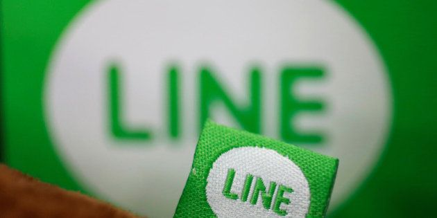 The logo of free messaging app Line is pictured on a smartphone and the company's stuffed toy in this...