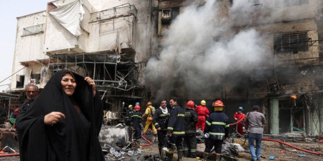 Iraqi firefighters extinguish a fire following a deadly suicide car bomb attack in the New Baghdad neighborhood...