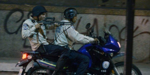 A policeman riding on a bike aims his shotgun during clashes with opposition activists in Caracas, on...
