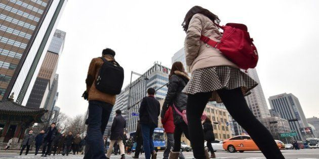 Pedestrians cross an intersection in the business district in Seoul on January 14, 2015. South Korea's...
