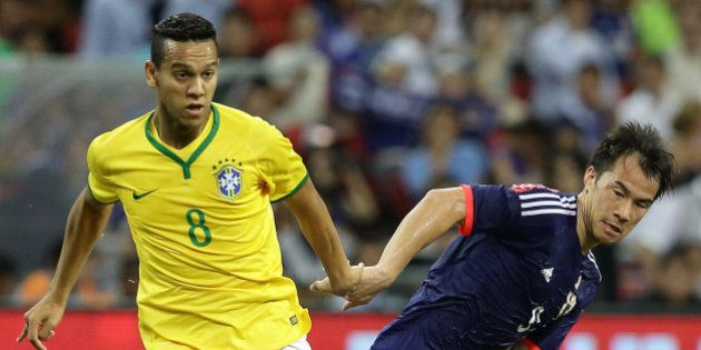 SINGAPORE - OCTOBER 14: Josef Souza of Brazil (L) and Shinji Okazaki of Japan challenge for the ball...