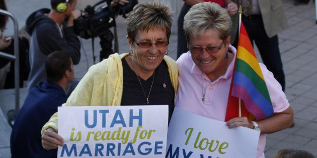 SALT LAKE CITY, UT - OCTOBER 6: People hold signs and cheer at a same-sex marriage victory celebration...