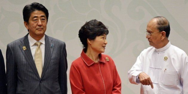 (L-R) Japanese Prime Minister Shinzo Abe looks on as South Korean President Park Geun-Hye speaks with...
