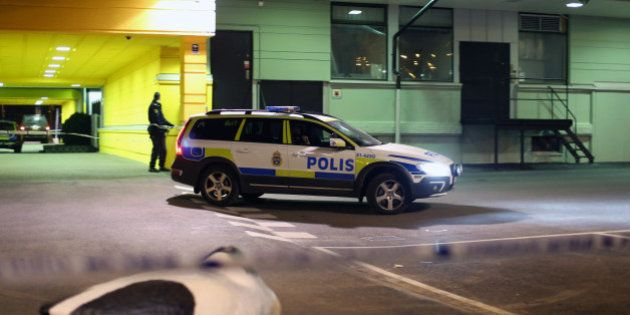 A police officer examines the scene of a fatal shooting in Gothenburg, Sweden, late Wednesday, March...