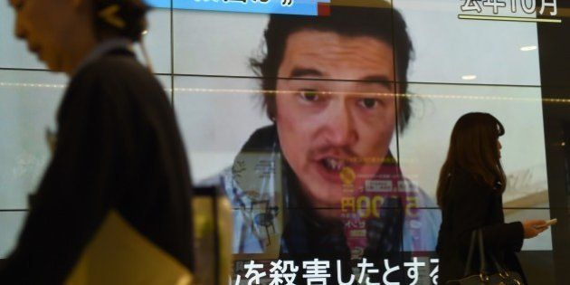 People walk past a big screen reporting that a Japanese hostage was killed by the Islamic State in Tokyo...