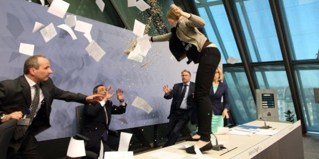 A woman interrupts a press conference by Mario Draghi (C), President of the European Central Bank, (ECB)...