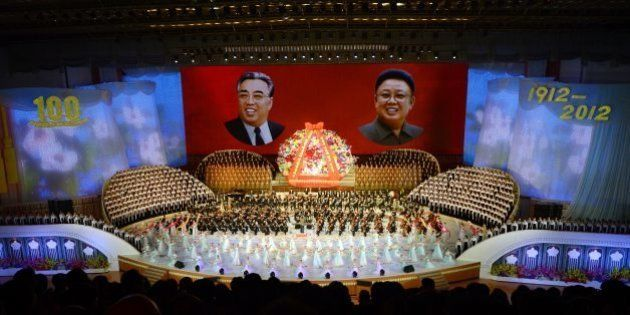 North Koreans performers sing in front of portraits of founding president Kim Il-Sung (L) and his son...