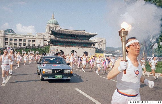 1988年9月16日、ソウルオリンピックを翌日に控え、ソウル中心部の光化門前を走る聖火ランナー。光化門の後ろに建つのは、旧朝鮮総督府庁舎だった国立中央博物館(1995年撤去)