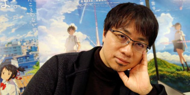 Japanese anime director Makoto Shinkai poses for a photo in front of posters of his animated film 'Your...