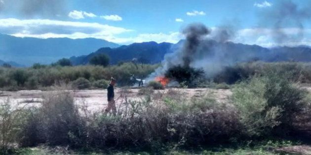 A man stands near the smoking remains of a helicopter that crashed with another near Villa Castelli in...