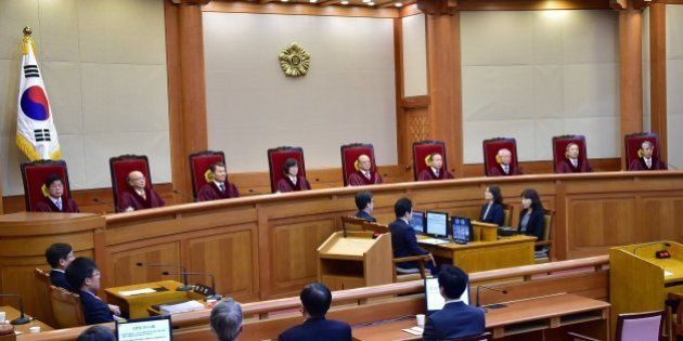 Park Han-Chul (top C), the chief judge of South Korea's Constitutional Court, delivers judgment on the...