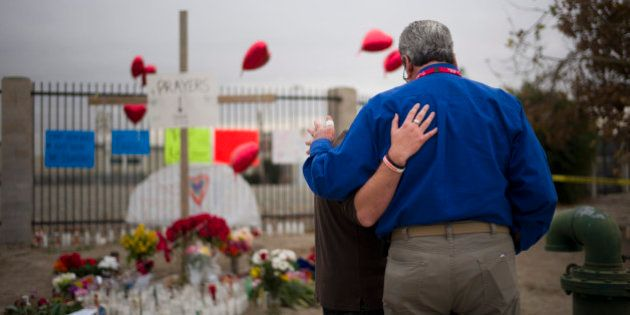 Chaplain Chuck Bender, right, prays with Michael Davila at a makeshift memorial honoring the victims...