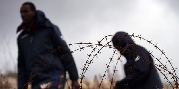LAMPEDUSA, ITALY - FEBRUARY 19: Migrants walk past barbed wire fences at the Temporary Permanence Centre...