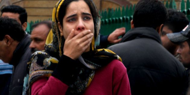SRINAGAR, INDIA - OCTOBER 26: A woman cries as she along with others rushed out of buildings following...