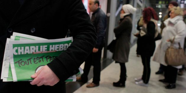 A man leaves after buying Charlie Hebdo newspapers as people queue at a newsstand in Paris, Wednesday,...