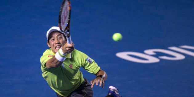 Kei Nishikori of Japan, returns the ball to David Ferrer of Spain, during the final of the men's singles...
