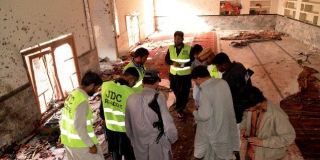 Pakistani investigators and security officials look for forensic evidence at a Shiite mosque in Shikarpur,...