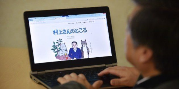 This photo illustration shows a man looking at newly opened website 'Murakami-san no tokoro' or 'Mr. Murakami's place' illustrated by artist Masaru Fujimoto, in Tokyo on January 16, 2015. Japanese novelist Haruki Murakami has started offering opinions and advice on queries from fans in an online agony uncle column, kicking things off by revealing his fears over hate speech and his own failing eyesight.   AFP PHOTO / KAZUHIRO NOGI        (Photo credit should read KAZUHIRO NOGI/AFP/Getty Images)