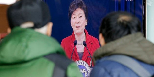 People watch a live broadcast of South Korean President Park Geun-hye's New Year press conference at...