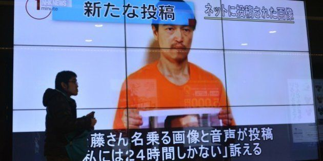 A pedestrian looks at a large screen in Tokyo on January 28, 2015 showing television news reports about...