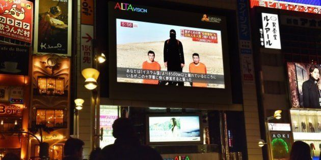 People look at a large TV screen in Tokyo on January 20, 2015 showing news reports about two Japanese...