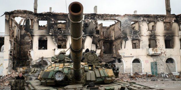 A pro-Russian rebel walks next to a destroyed tank on February 7, 2015 in the eastern Ukrainian town...