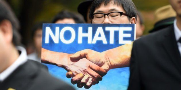 A protesters holds a banner against racism as he marches on a street in Tokyo on November 2, 2014. The...