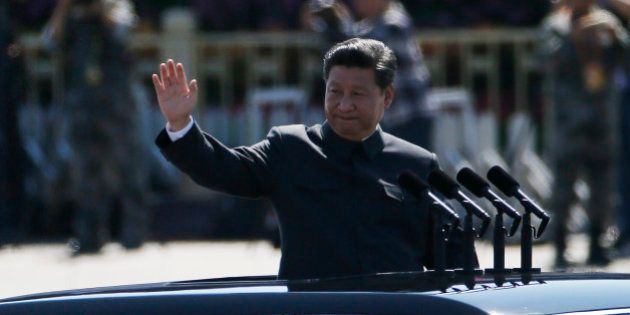 Chinese President Xi Jinping stands in a car and waves during a troop review during a parade commemorating...
