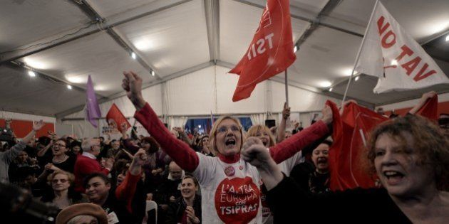 Anti-austerity Syriza supporters celebrate after the first exit polls, as they gather at the Syriza election...