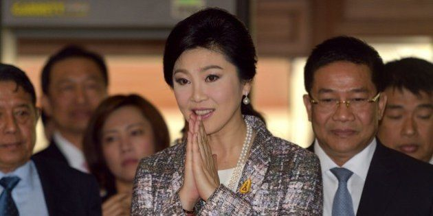 Ousted Thai prime minister Yingluck Shinawatra (C) gestures a traditional greeting to members of the...