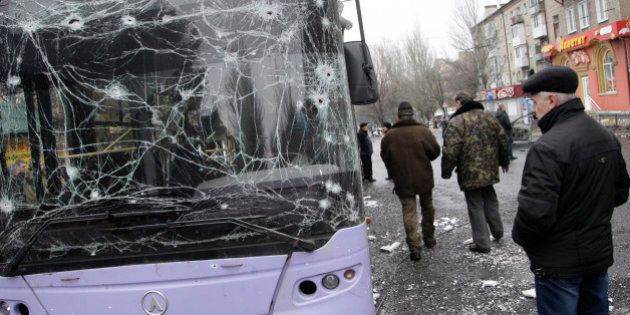 DONETSK, UKRAINE - JANUARY 22 : People gather next to a damaged bus after a mortar shell hit near bus...