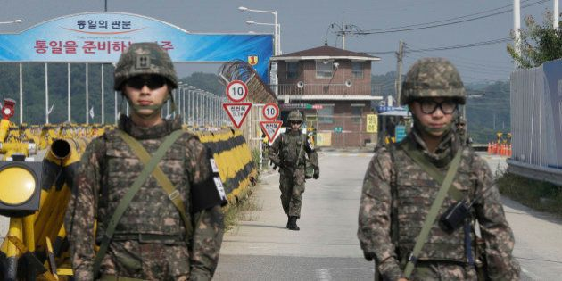 A South Korean amy soldier walks as his colleague soldiers stand guard on Unification Bridge, which leads...