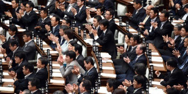 Ruling party lawmakers applaud a supporting speech for Japan's Prime Minister Shinzo Abe (not pictured)...